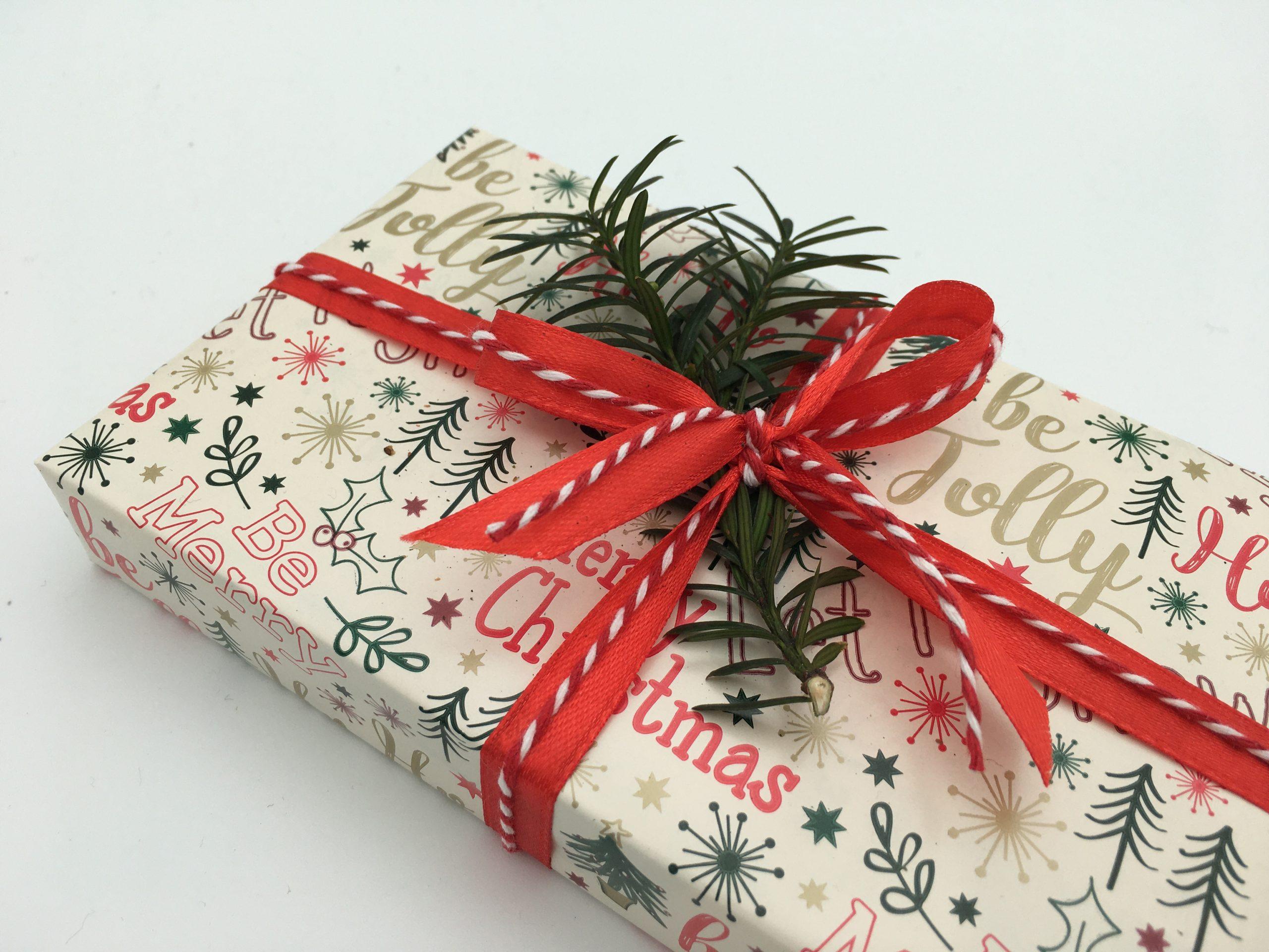 Julklapp med textat julpapper och rött satinband