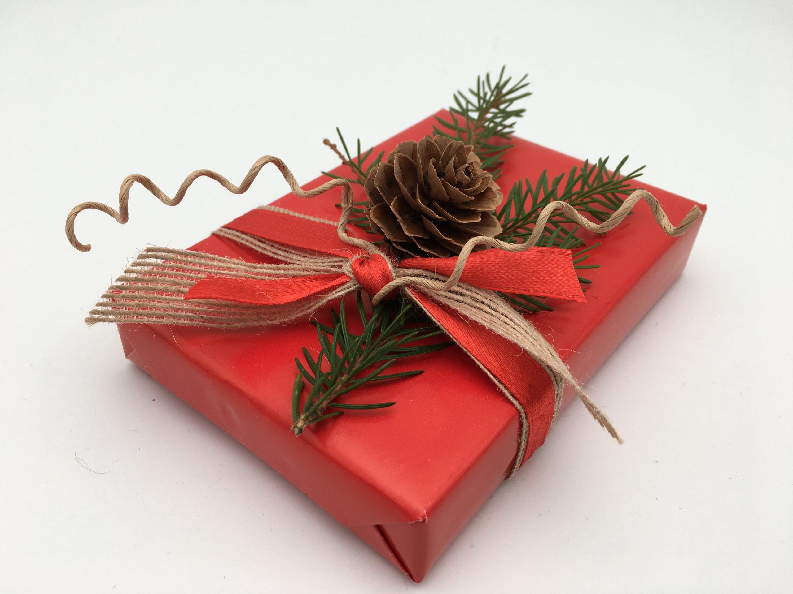 Julklapp i rött med grankvist och kotte