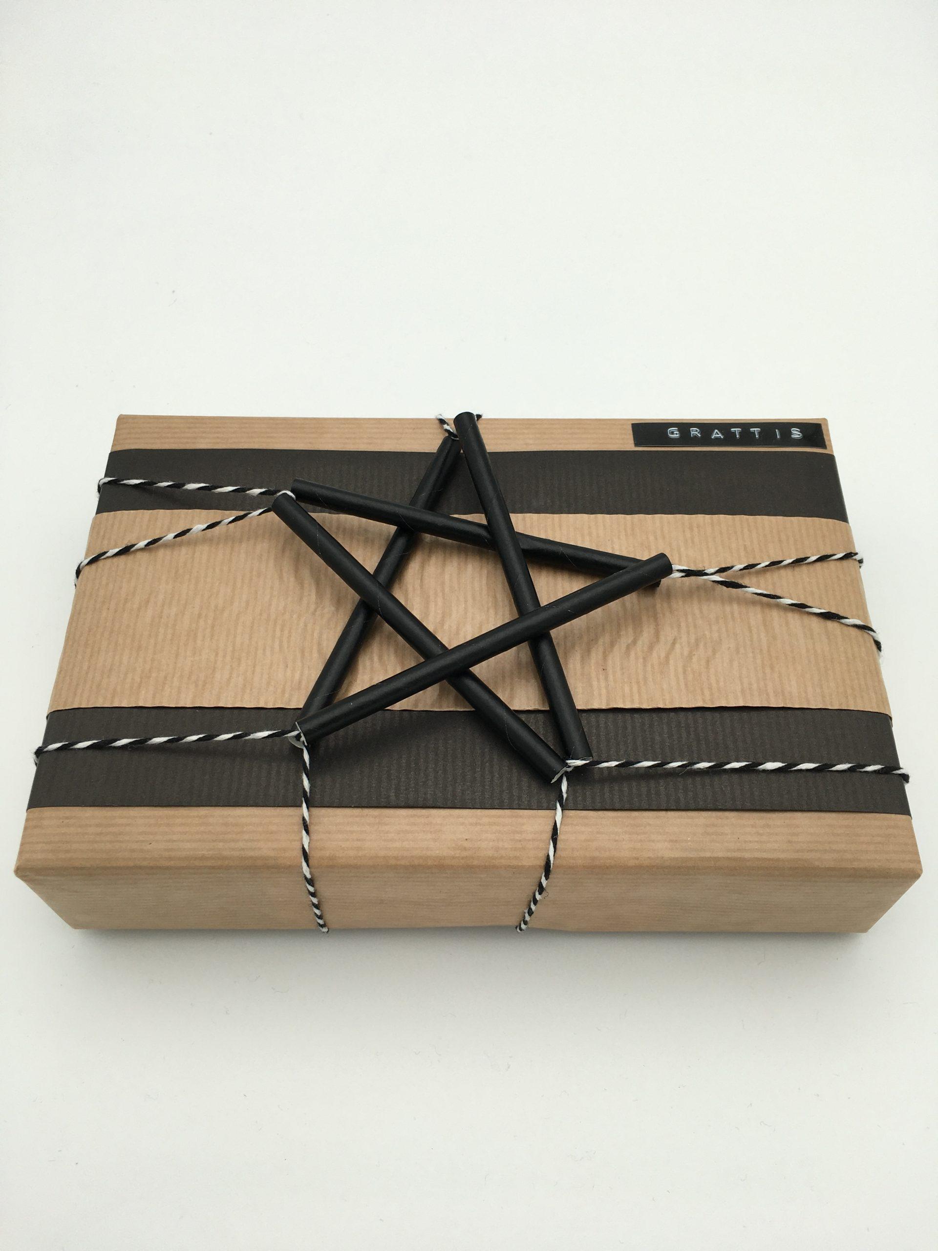 Present i svart och natur med stjärna av papperssugrör