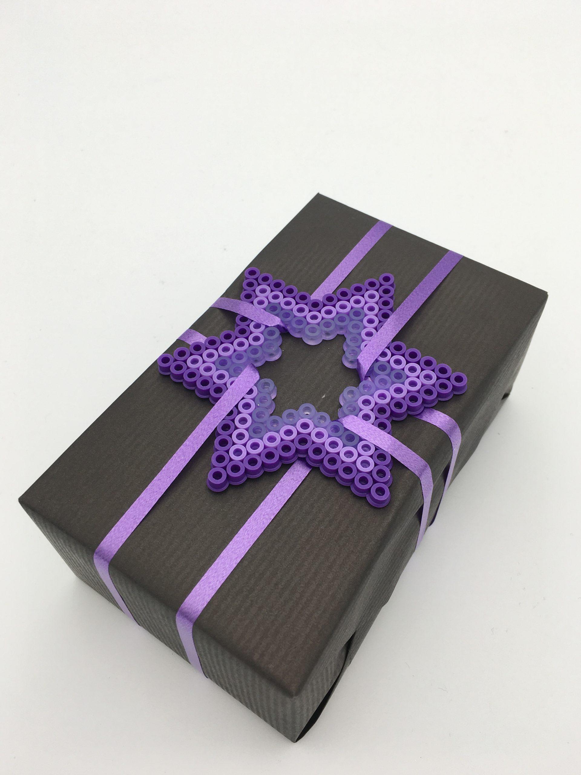 Present i svart och lila med pärlad stjärna